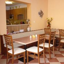 Společná místnost v pozadí s kuchyňkou.