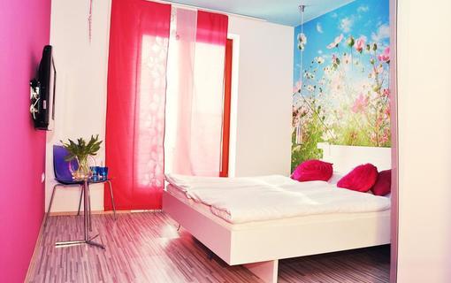 Design hotel RomantiCK Klasik pokoj Kohoutek luční v zářivých barvách.
